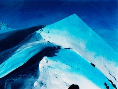 Heureuse coïncidence: au moment où l'on peut visiter la magnifique exposition sur la peinture Suisse entre réalisme et idéal, l848-l906 (au Musée Rath à Genève jusqu'au 13 septembre 1998), paraît un savoureux opuscule intitulé La Montagne bleue. Fruit d'un duo formé de l'écrivain Jean-Michel Olivier et du photographe Jacques Pugin, tous deux Genevois, cette plaquette mérite le détour. Et pour pas mal de raisons. C'est un bel objet, conçu à l'ancienne et sous cellophane comme savent le concocter les éditions neuchâteloises Ides et Calendes, spécialisées dans les ouvrages d'art. Avant de mériter son contenu, tout comme le randonneur en quête de sommet, le lecteur doit payer de sa personne en découpant les pages. loin de nos mœurs impatientes, l'exercice n'en est pas pour autant rébarbatif. En délivrant ainsi les feuillets à l'aide d'un coupe-papier, le lecteur participe à la construction du livre.